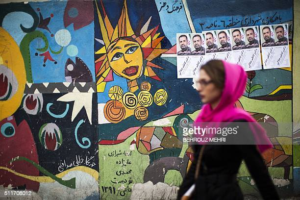 An Iranian woman walks past a mural bearing electoral posters of reformist candidate Kazem Jalali in downtown Tehran on February 22 2016 ahed of the...
