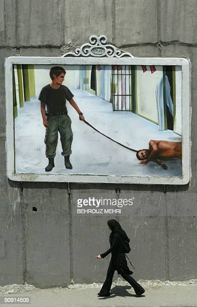An Iranian woman walks past a mural depicting a scene from the torture of Iraqi prisoners by US soldiers at the Abu Ghraib prison near Baghdad on a...