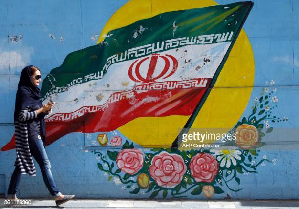 An Iranian woman walks past a mural of the Iranian flag in the capital Tehran on October 14 2017 Iranians responded with anger and mockery on...