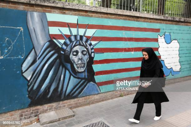 An Iranian woman walks past a mural on the wall of the former US embassy in the Iranian capital Tehran on May 8 2018 US President Donald Trump is due...