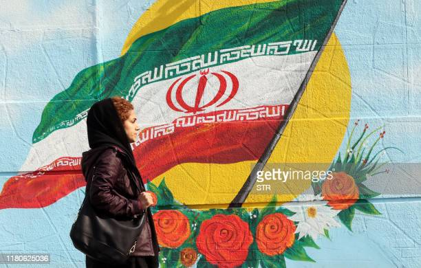 An Iranian woman walks past a mural painting of the Islamic republic's national flag in central Tehran on November 7 2019. - Iran resumed uranium...