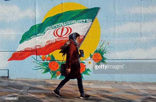 An Iranian woman walks past a mural painting of the Islamic republic's national flag in central Tehran on November 21, 2019.
