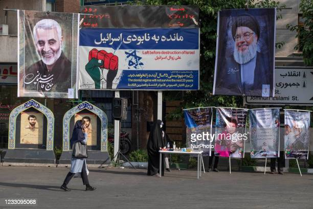 An Iranian woman walks past a portrait of Iranian former Islamic Revolutionary Guard Corps Quds Force General Qasem Soleimani , who has killed in an...