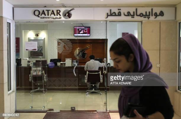 An Iranian woman walks past a Qatar Airways branch in the capital Tehran on June 6 2017 A ban on Qatari flights imposed by Saudi Arabia and its...