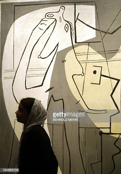 An Iranian woman walks past a sculpture by 20th century painter and sculptor Pablo Picasso after the inauguration of the Modern Art Movement...