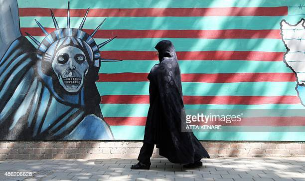 An Iranian woman walks past an antiUS mural depicting the Statue of Liberty on the wall of the former American embassy in Tehran on September 2...