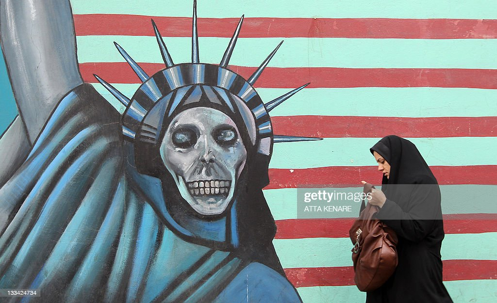 An Iranian woman walks past an anti-US mural painted on the wall of the former US embassy in Tehran on November 19, 2011. The United States said Iran was now locked in 'unprecedented' isolation after UN bodies overwhelmingly condemned its nuclear programme and an alleged Tehran-planned terror plot.