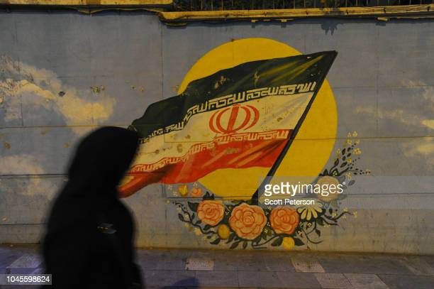 An Iranian woman walks past an Iranian flag painted on a wall as Iranians try to lead normal lives while bracing for renewed US sanctions on...