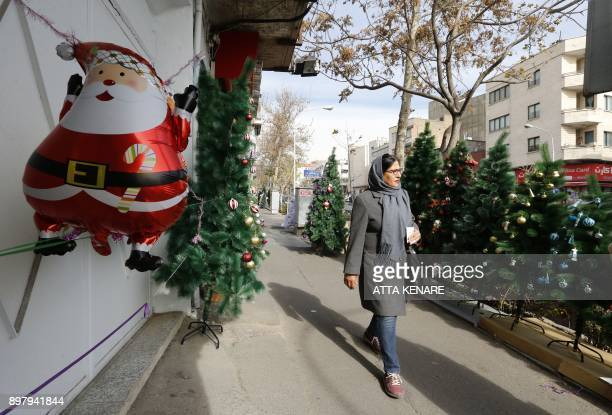 An Iranian woman walks past Christmas decorations in a street in the capital Tehran on December 24 on Christmas eve / AFP PHOTO / ATTA KENARE