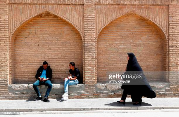 TOPSHOT An Iranian woman walks past men resting on the SioSe Pol bridge over the Zayandeh Rud river in Isfahan which now runs dry due to water...