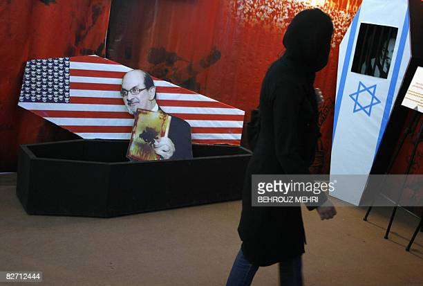 An Iranian woman walks past mock coffins bearing a US flag where skulls have replaced its stars and an Israeli flag along with pictures of Indianborn...