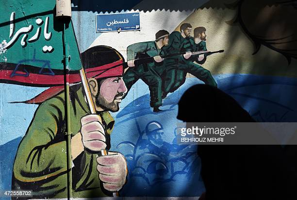 An Iranian woman walks past murals of Iranian soldiers marching during the IranIraq war on May 8 on Palestine square in Tehran after a demonstration...