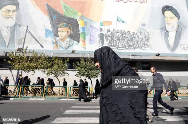 An Iranian woman walks past pictures of Iranian supreme leader Ayatollah Ali Khamenei and of late Iranian supreme leader Ayatollah Ruhollah Khomeini...
