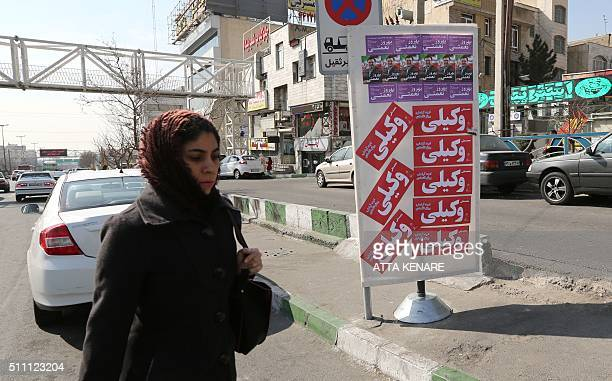 An Iranian woman walks past stickers in support of Mohammad Ali Vakili a candidate for the upcoming parliamentary elections in a street in downtown...