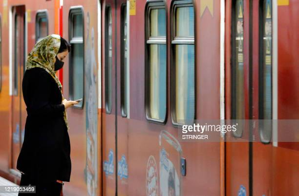 An Iranian woman wearing a face mask waits for a train carriage at a metro station in the capital Tehran on June 10, 2020 amid the coronavirus...