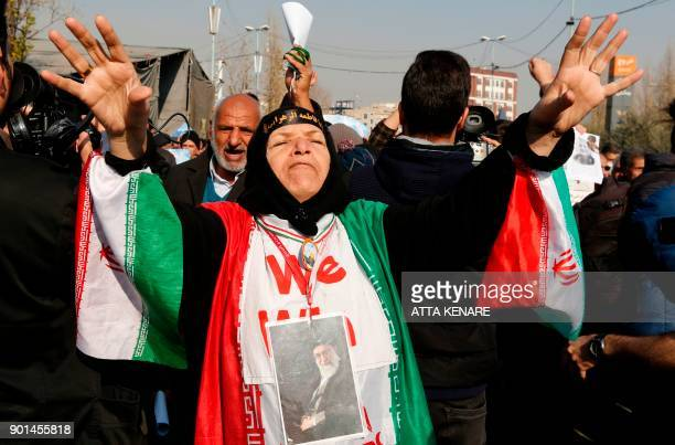 An Iranian woman wearing a portrait of Supreme leader Ayatollah Ali Khamenei around her neck and the colours of the national flag shouts slogans...