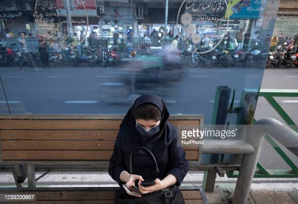 An Iranian woman wearing a protective face mask uses her smartphone while sitting at a bus-stand near a crossroad in downtown Tehran on May 30, 2021....