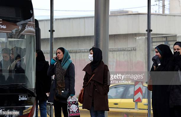An Iranian woman wears a face mask at a bus stop in Tehran as pollution engulfs the city on December 30 2015 Exhaust fumes from the five million cars...
