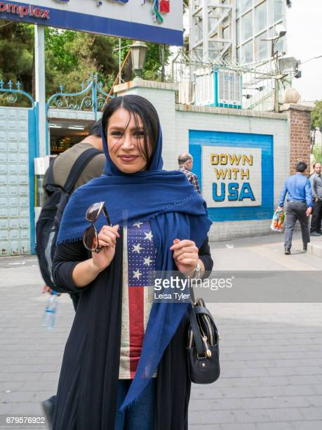 An Iranian woman wears a teeshirt of the American flag beside a slogan calling for the fall of America outside the former USA Embassy in Tehran The...
