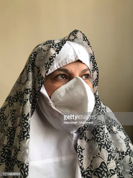 an iranian woman with mask at home, during quarantine for corona virus - nowruz stock pictures, royalty-free photos & images