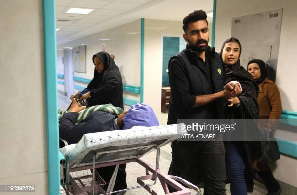 An Iranian woman wounded in a stampede that broke out at the funeral of Revolutionary Guards commander Qasem Soleimani is wheeld into a ward in...