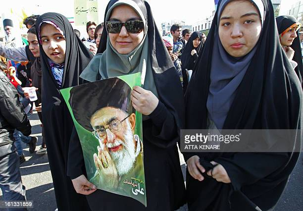 An Iranian women holding a portrait of the founder of Iran's Islamic Republic Ayatollah Ruhollah Khomeini attends a rally in Tehran's Azadi Square to...