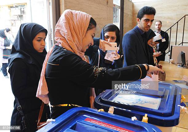 An Iranian women takes a photo with her mobile phone of her friend casting a ballot in key elections for Parliament and the Assembly of Experts in...
