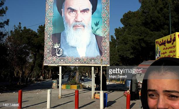 An Iranian women walk past a picture of Iran's late Leader Ayatollah Khomeini at the entrance of Beheshte Zahra cemetery on February 27 2012 in...