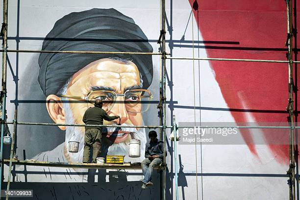 An Iranian worker puts the final touches to a mural of Iran's supreme leader, Ayatollah Ali Khamenei, at Enghelab square on February 27, 2012 in...