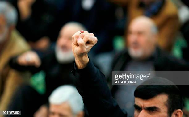 An Iranian worshipper raises his fist during the friday prayers at the Imam Khomeini mosque in Tehran on January 5 2018 New proregime protests were...