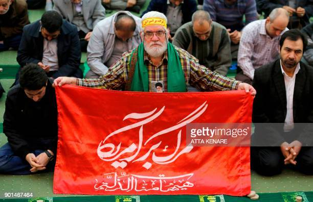 An Iranian worshipper wearing a portrait of Supreme leader Ayatollah Ali Khamenei around his neck attends the friday prayers at the Imam Khomeini...