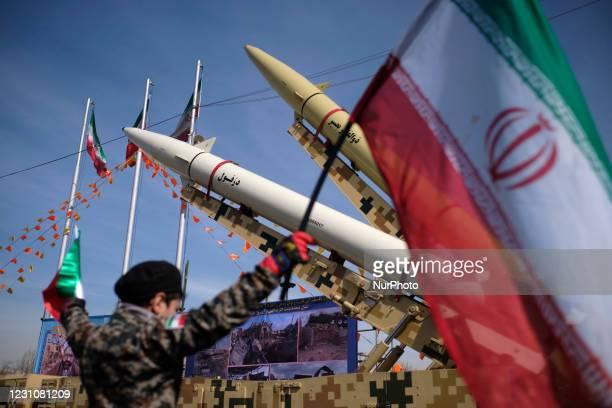 An Iranian young boy wearing an Islamic Revolutionary Guard Corps uniform holds an Iran flag while Iran-made, Dezful medium range ballistic missile...
