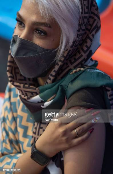 An Iranian young woman wearing a protective face mask looks on as she holds a band aids on her arm after receiving a dose of China's Sinopharm new...