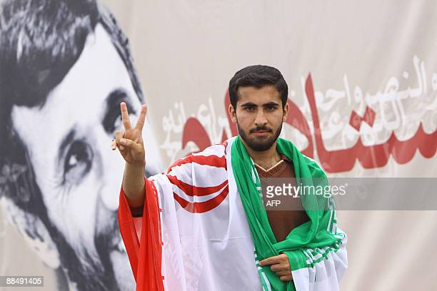 An Iranian youth, with a national flag on his shoulders, flashes the v-sign of victory during celebrations of President Mahmoud Ahmadinejad's...