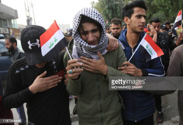 An Iraq youth cries during the funeral procession of a prominent civil society activist who was shot dead the previous night while returning home...
