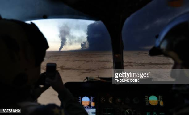 An Iraqi airforce pilot takes a picture of the black plumes of smoke from burning oil wells, set ablaze by retreating Islamic State group's...