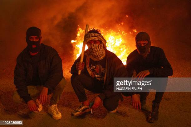 An Iraqi anti-government demonstrators gather in front of burning tyres during a protest in the southern city of Basra on February 25, 2020.