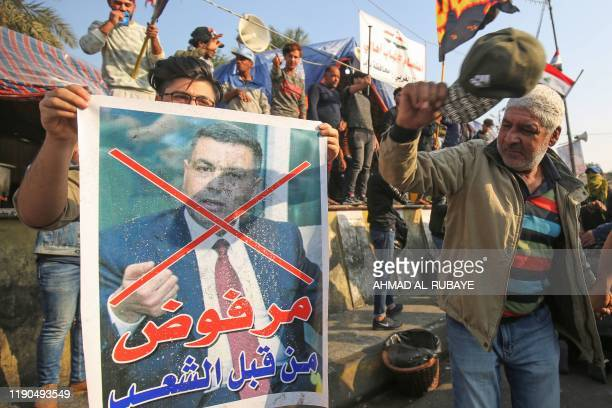 An Iraqi anti-government protester beats with his cap a defaced poster of Assaad al-Aidani, the governor of Basra, during a demonstration in...