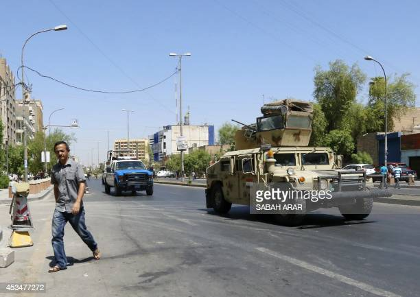 An Iraqi army armoured vehicle patrols a street in Baghdad's commercial district of Karrada on August 11 2014 as security measures have been...