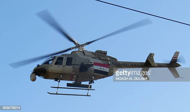 An Iraqi army Bell 407 helicopter flies over the Sufiya district on the outskirts of Ramadi as security forces on the ground clear the area on...