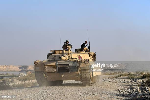 An Iraqi army M1 Abrams tank approaches a checkpoint on October 21 2016 near Qayyarah Iraq Several hundred Iraqi families have been made to leave...