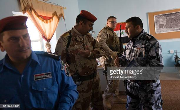 An Iraqi Army officer, center, speaks with a Husayba police commander, right, as a U.S. Marine officer waits nearby following their weekly meeting...