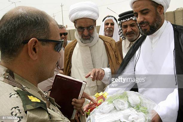 An Iraqi army officer receives a gift of flowers and a Koran from representatives of the Shiite movement of cleric Moqtada alSadr in Basra 550 kms...
