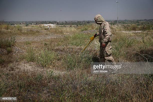 An Iraqi Army soldier checks for chemical weapons as a forensics team unearths corpses from mass graves in the palace compound of former Iraqi...