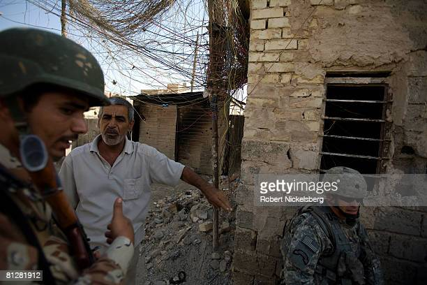 An Iraqi Army soldier left helps local Shiite residents of Sadr City remove a large IED hidden by militias inside a generator room in the southern...