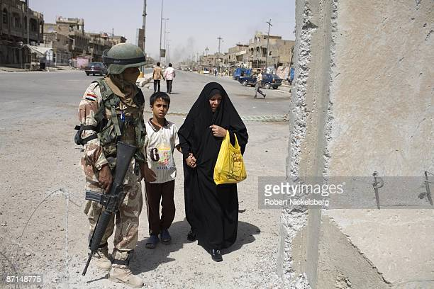 An Iraqi Army soldier monitors civilians crossing the concrete barrier dividing Sadr City the 25 million Shia dominated stronghold of cleric Moktada...