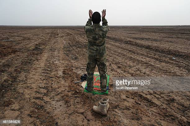 An Iraqi Army soldier of the Iraqi 5th Division prays along a new dirt road made to ease the fight against Islamic State militants in Diyala Province...