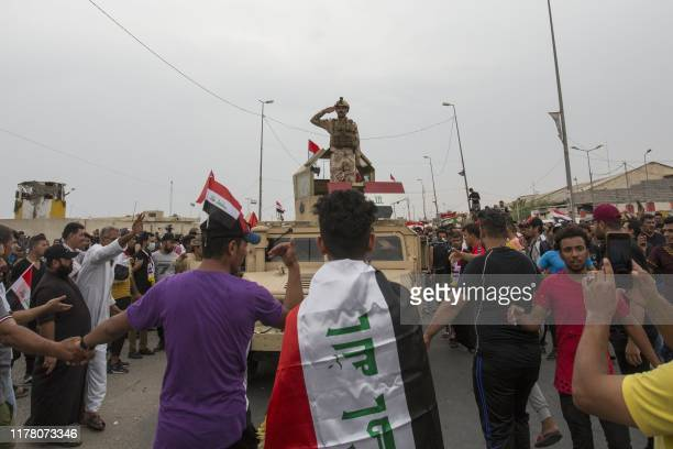 An Iraqi army soldier standing atop a humvee gestures while saluting protesters gathering during an anti-government demonstration outside the local...