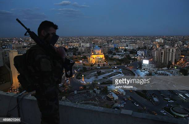 An Iraqi Army soldier stands guard atop the Palestine Hotel overlooking Firdos Square where a statue of Saddam Hussein was toppled during the US...