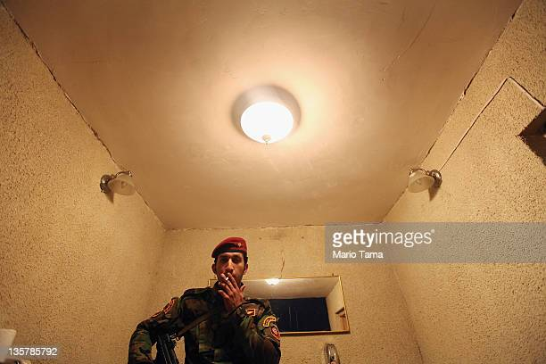 An Iraqi Army special forces soldier smokes outside a women's art exhibition sponsored by Iraqi Parliament member Safi Asiheil in a posh Baghdad...